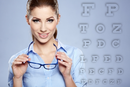 eye chart: woman with  trendy glasses on the background of eye test chart  Stock Photo