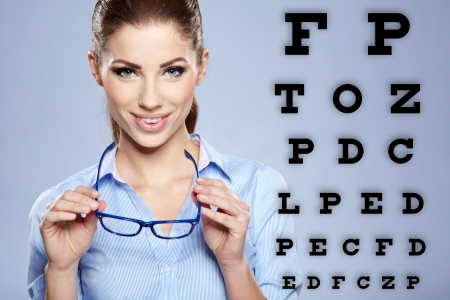 woman with  trendy glasses on the background of eye test chart  photo