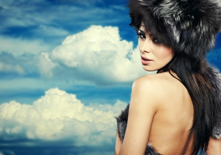 Fur Fashion  Beautiful Girl in Fur Hat  Winter Woman Portrait on sky photo