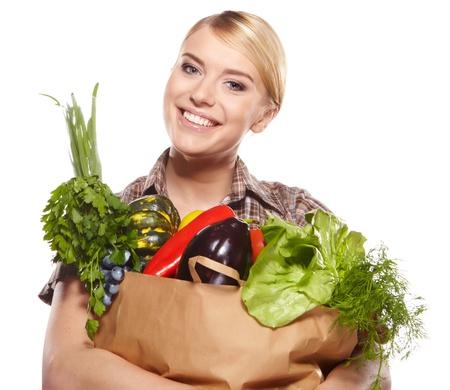 bolsa de pan: mujer que sostiene un bolso de compras lleno de tiendas de comestibles, mango, ensalada, rábanos, limón, zanahoria en el fondo blanco