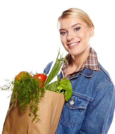canned goods: woman holding a shopping bag full of groceries, mango, salad,  radish, lemon, carrots on white background