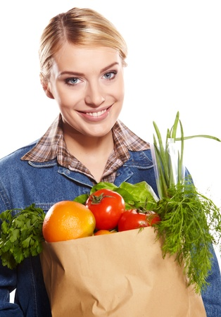 woman holding a shopping bag full of groceries, mango, salad,  radish, lemon, carrots on white background photo