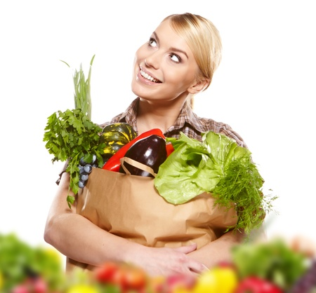 Portrait of happy young woman holding a shopping bag full of groceries on white background  photo