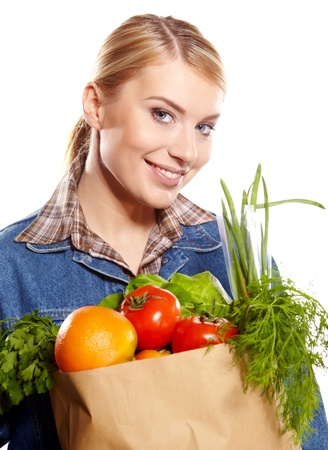 Portrait of happy young woman holding a shopping bag full of groceries on white background  Stock Photo - 17564554