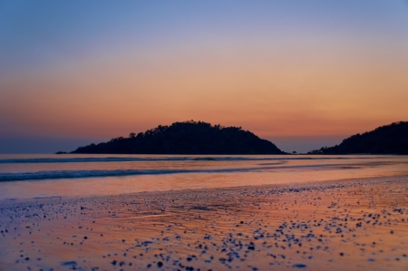 Empty beach, boat in the sea, waves and sunset in Goa in India  photo