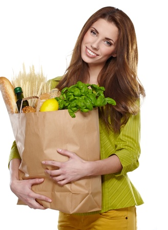 Young woman holding a grocery bag full of fresh and healthy food photo