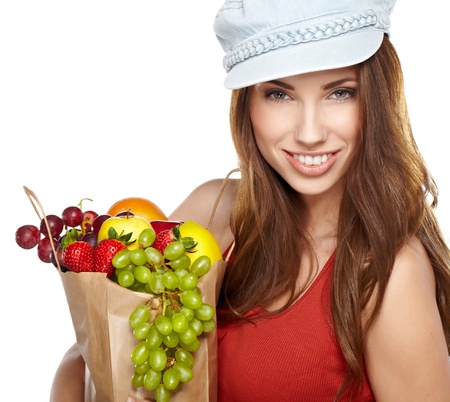 Portrait of happy young female holding a shopping bag full of groceries on white background  photo