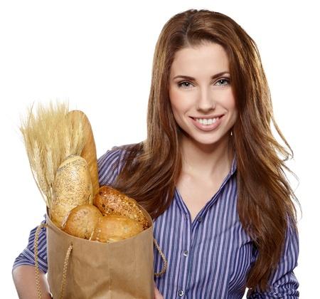 bolsa de pan: Retrato de la mujer joven sonriente que sostiene un bolso de compras lleno de tiendas de comestibles en el fondo blanco