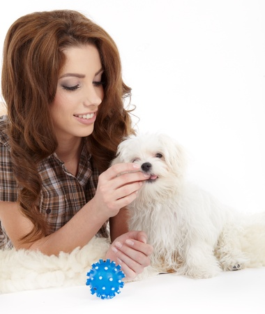 beautiful girl with perfect skin and long wavy hair with a fluffy white dog on a white background  photo