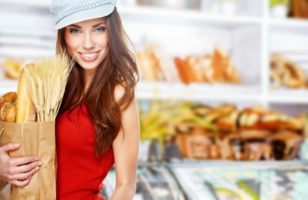 Young woman holding a grocery bag full of bread photo