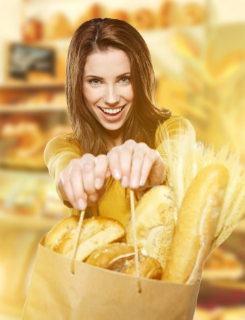 bolsa de pan: Mujer joven que sostiene una bolsa de papel llena de pan Foto de archivo