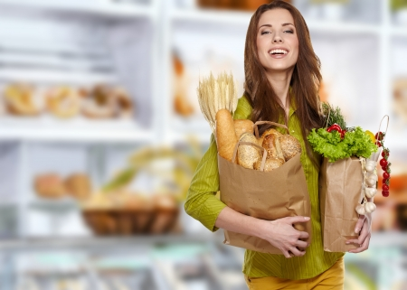 happy shopper: Young woman holding a grocery bag full of bread