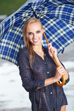 Beautiful blonde woman holding umbrella out in the spring rain  photo