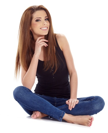 squatter: Beautiful brunette woman sitting on the floor   Studio shoot  Stock Photo