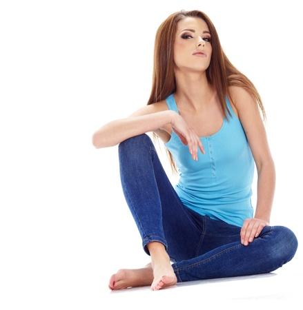 squatter: Beautiful brunette woman sitting on the floor . Studio shoot. Stock Photo