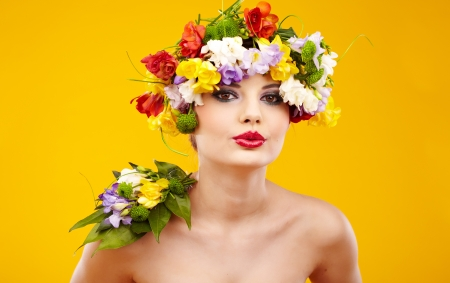 Woman with hairstyle and flower. Isolated on yellow photo