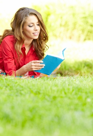 lying on grass: beautiful girl with book in  park  Stock Photo