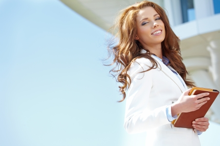 Beautiful young businesswoman among the skyscrapers of the modern business center  photo