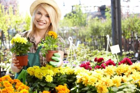 garden center: Garden center worker smiling and holding up yellow flower  Stock Photo