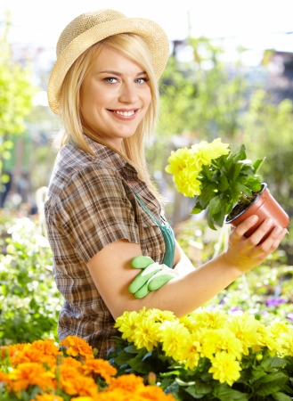 pot light: Garden center worker smiling and holding up yellow flower  Stock Photo