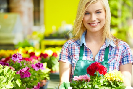 garden center: Woman holding a flower box while smiling