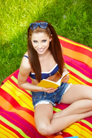 Young smiling woman reading in summer park  photo