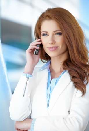 Beautiful business woman talking on cell phone while looking at copyspace  photo