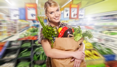 produce sections: woman shopping for fruits and vegetables in produce department of a grocery storesupermarket