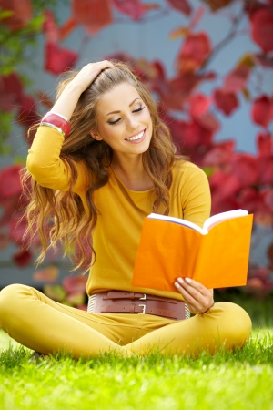 woman reading book: college student studying at campus