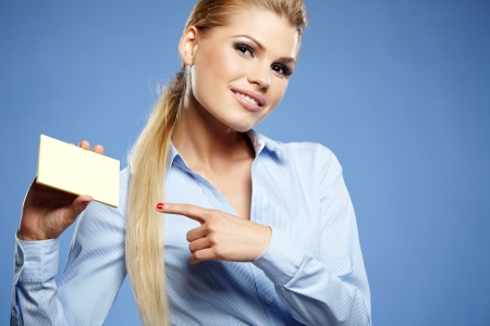 Businesswoman holding credit card. Isolated on blue Stock Photo - 19875044