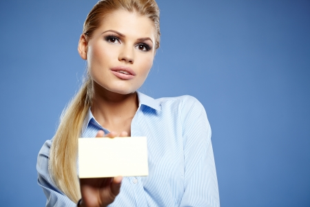 businesscard: Businesswoman holding credit card. Isolated on blue Stock Photo
