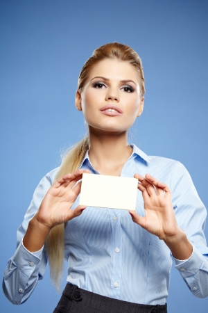Businesswoman holding credit card. Isolated on blue Stock Photo - 19874865
