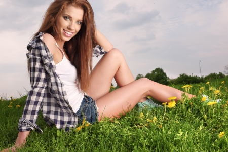 young beautiful brunette woman sitting on grass photo