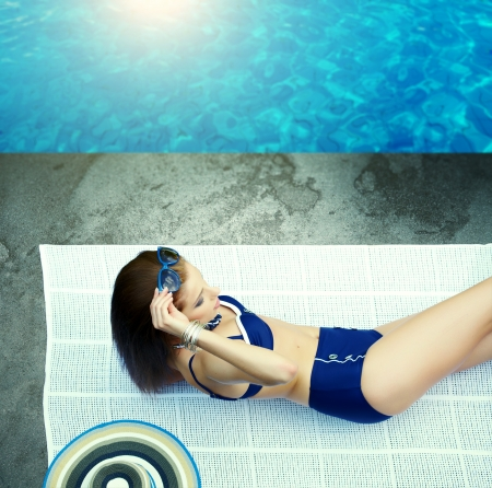 Beautiful young sexy woman by a swimming pool  photo