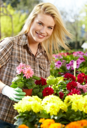 smiling woman in a greenhouse: Florists woman working with flowers at a greenhouse