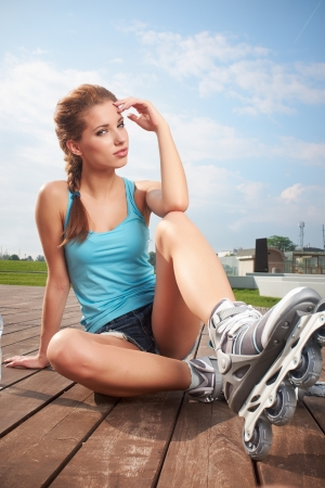 inline skater: Young woman putting on skates going rollerblading in urban city park  Stock Photo
