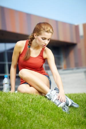 inline skater: Woman skating in city  Girl going rollerblading sitting in grass putting on inline skates  Stock Photo