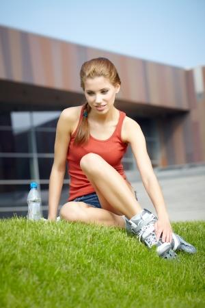 blading: Girl going rollerblading sitting in grass putting on inline skates  Stock Photo