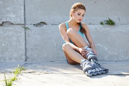 Roller girl putting on roller skates into her feet Stock Photo