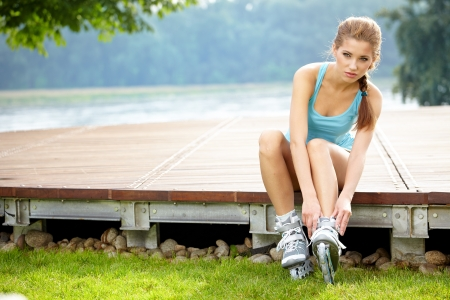 inline skater: Happy woman putting on roller skate in park sunny day  Stock Photo