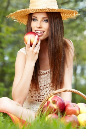 Apple woman  Very beautiful ethnic model eating red apple in the park   photo