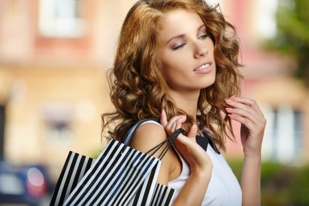 Fashionable girl in white dress with shopping bag  photo