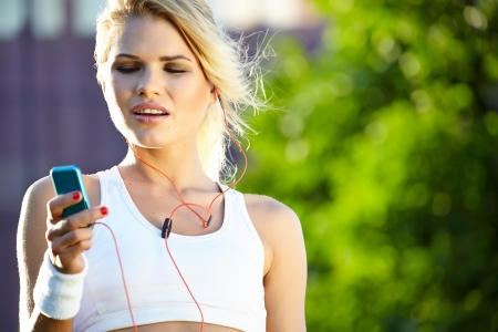 portable mp3 player: Stunning young blonde woman in pink sports bra rests and adjusting music on portable music player Stock Photo