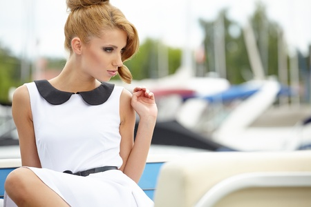 Bautiful sexy tanned brunette woman standing in a port fashion style, sea background, yachts  photo