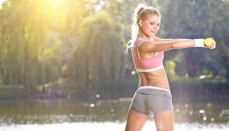 fitness: fêmea instrutor de fitness exercício com pequenos pesos no parque verde