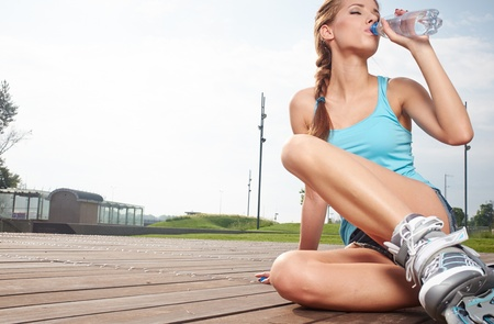 Young woman drinking water at outdoors workout  photo