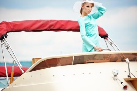 Elegant retro woman wear  dress , sitting near the wooden yacht  60