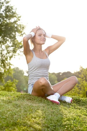 girl sit: Relax in grass - tired woman after sport