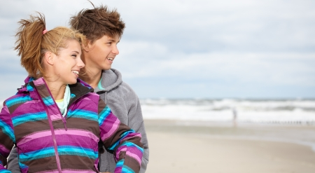 Couple embracing and having fun wearing warm clothes outside on coast behind blue sky  photo