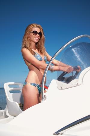 power boat: Beautiful woman driving a motor boat